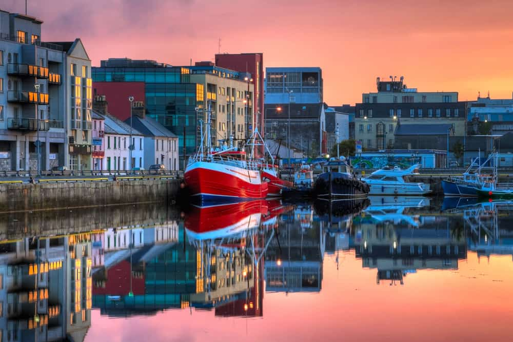 Galway Ireland - morning view on row of buildings and fishing boats in Galway Dock with sky reflected in the water, HDR image