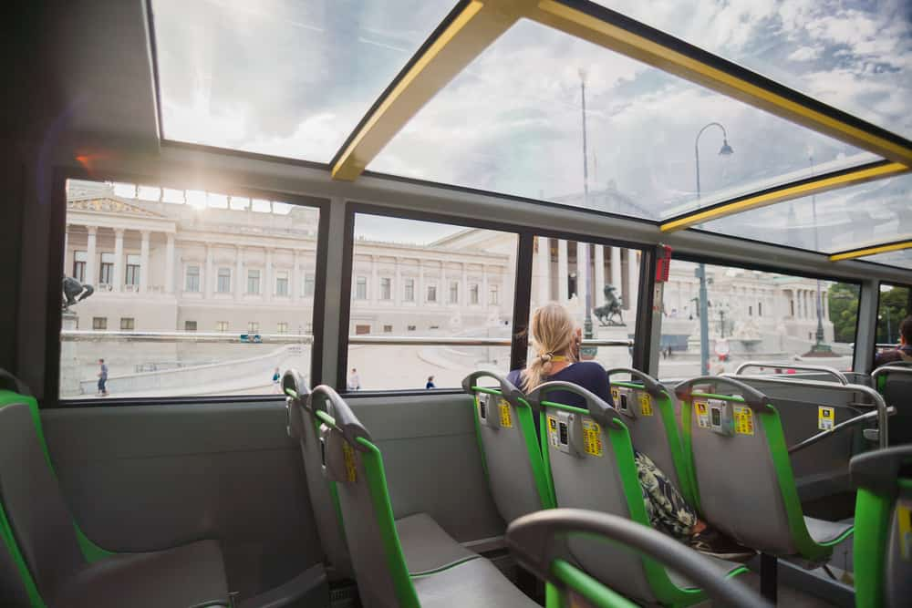 Woman sitting a back to the camera in a touristic bus and looking to sightseeing in Vienna