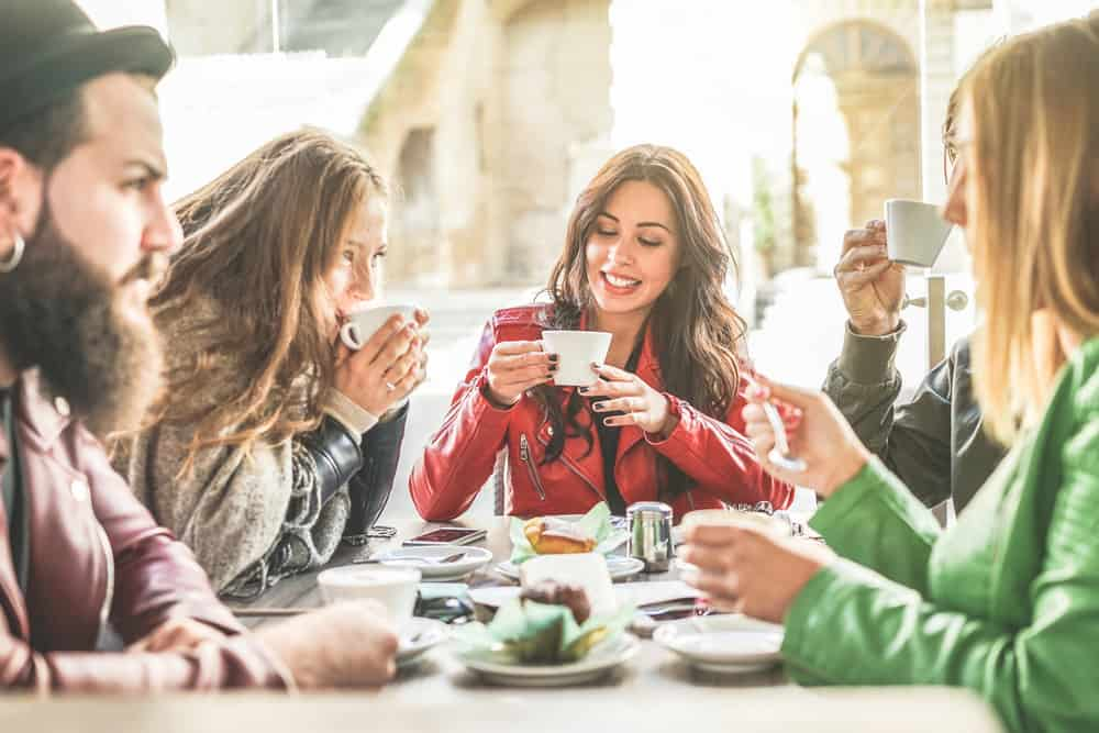 Italy - Milan - Young friends toasting coffee and doing breakfast in bar bakery shop - Happy hipster people drinking cappuccino and eating muffins - Friendship concept - Focus on center girl - Warm filter