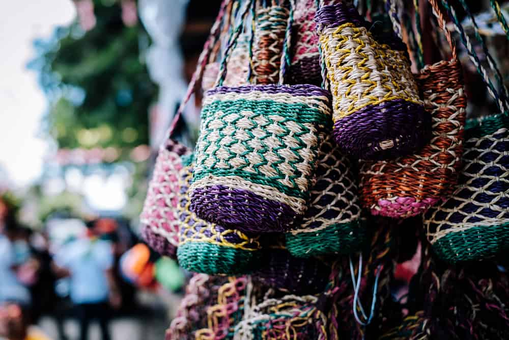 A bunch of colorful and handmade pouches or shoulder bags made from Manila hemp, a strong fiber obtained from the leafstalk of a banana native to the Philippines. Selective focus. Copy space.