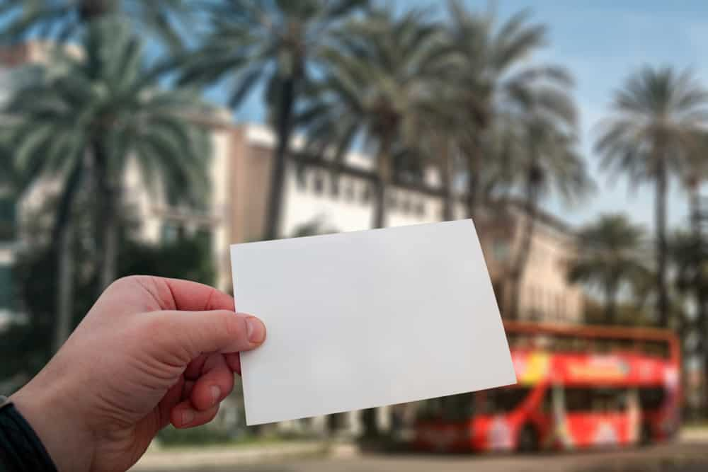 Spain - Palma - White postcard mockup in man's hand on the background palm trees and travel bus on Mallorca Island in Spain