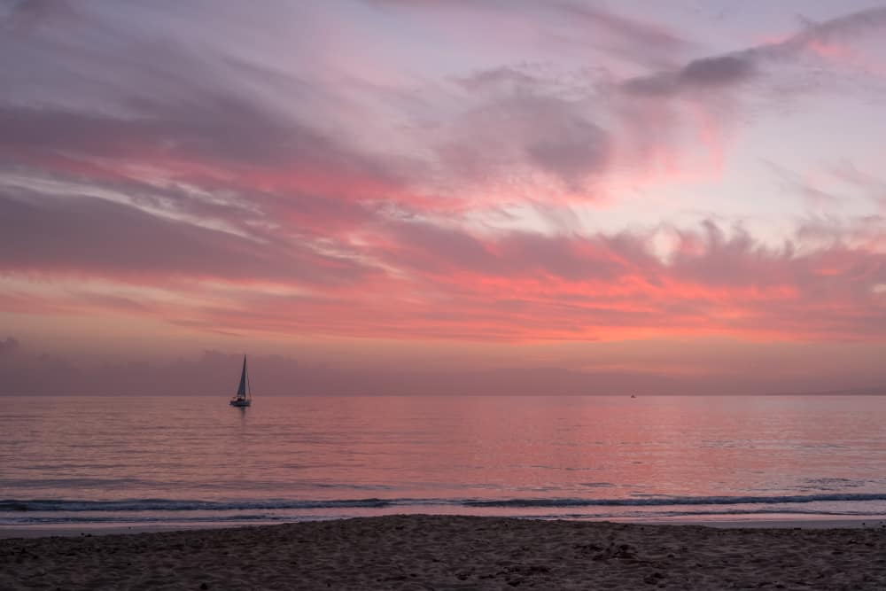Spain - Mallorca - Delicately colored clouds reflect reds, pinks, oranges, mauves and corals of winter sunset in quiet Platja de Palma, Mallorca
