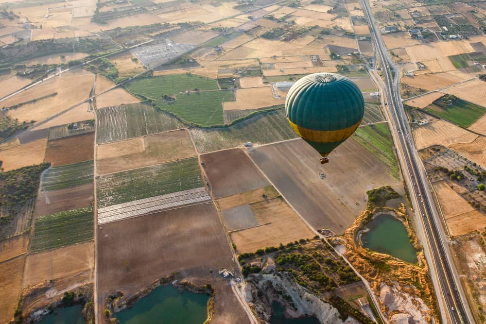 Spain - Mallorca - View of a balloon hovering in Mallorca over fields, road, lake.