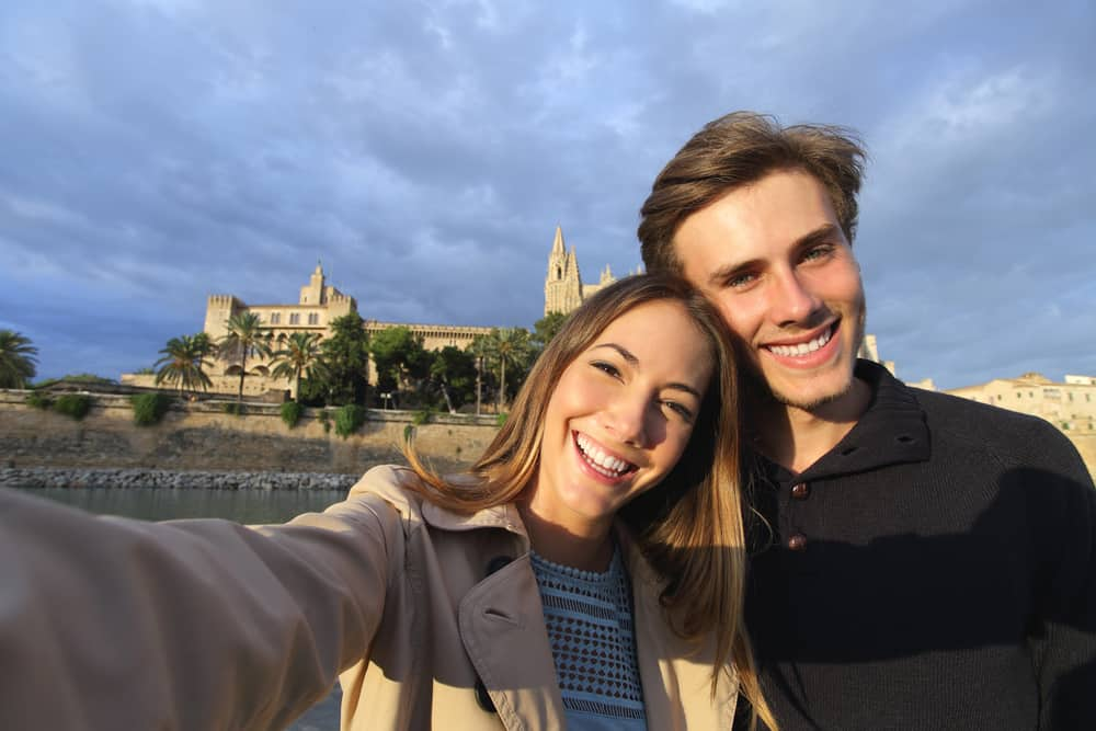Spain - Mallorca - Tourist couple on holidays photographing a selfie with Palma de Mallorca Cathedral in the background