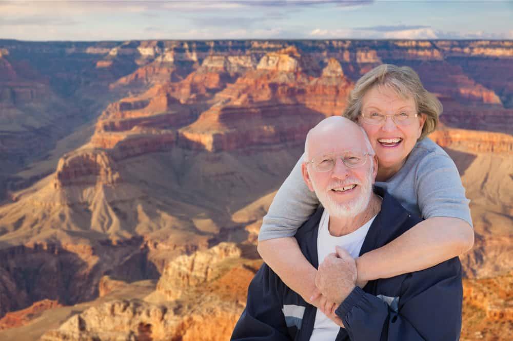 USA - Arizona - Grand Canyon - Happy, Hugging Senior Couple Posing on the Edge of The Grand Canyon.