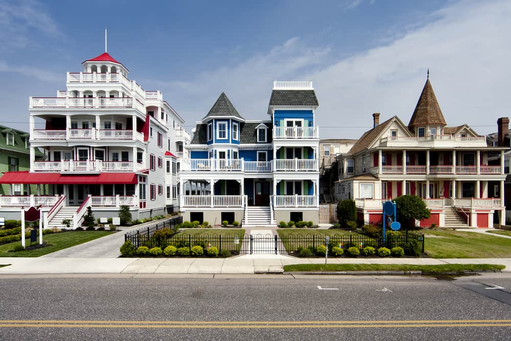USA - New Jersey - Colorful Victorian style houses alongside a road. Beautiful wooden homes with balconies and porches, painted red, blue, white and orange, under a blue summer spring sky, in Cape May, NJ.