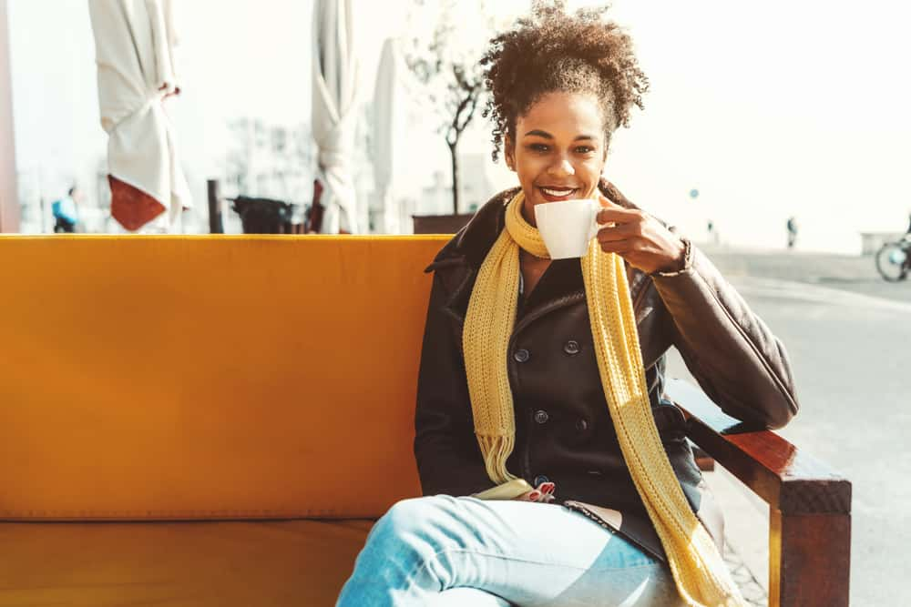 Portugal - Lisbon - A Dazzling young happy African-American female is drinking a delicious coffee drink in an outdoor bar; smiling Brazilian girl in demi-season coat and scarf is drinking tea in a cafe outdoors