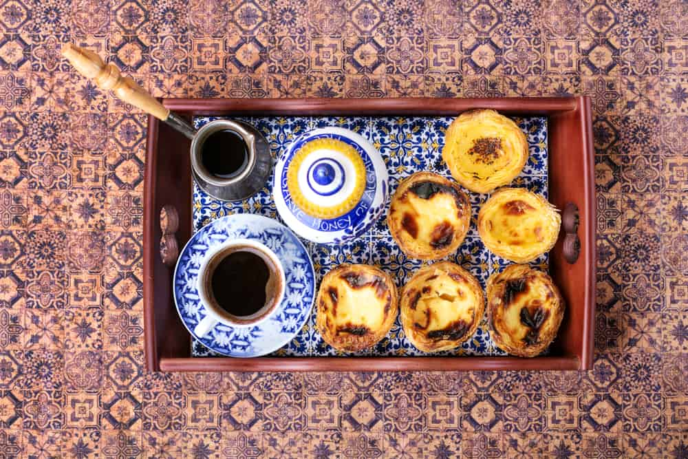 Portugal - Lisbon -  Traditional Portugese pastry Pastel de Nata served with coffee and honey on traditional tray over a rustic wooden board. Top View.