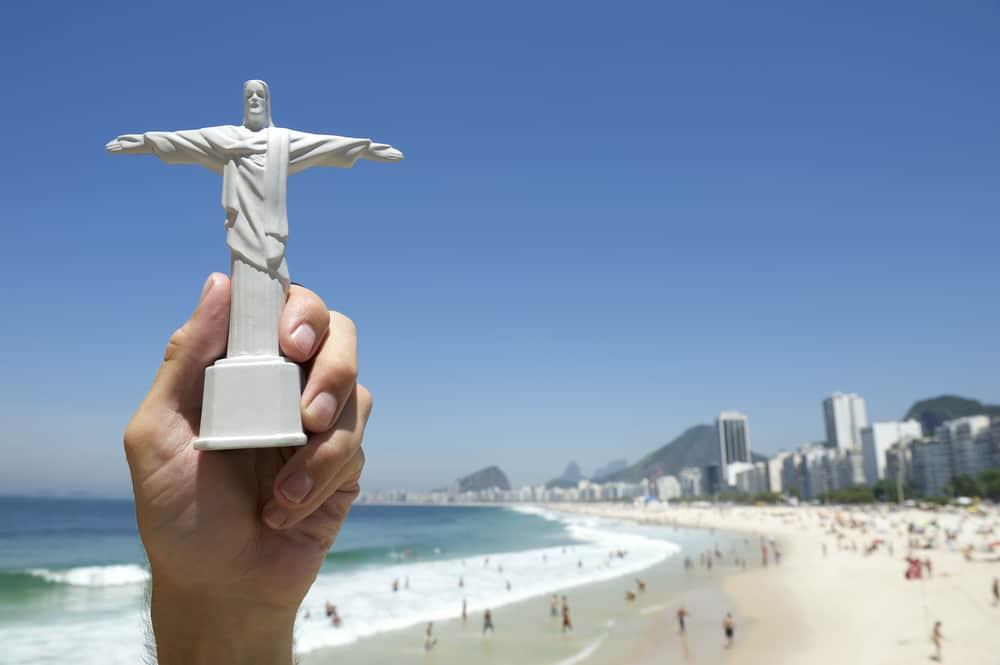 Tourist holding Corcovado Christ the Redeemer statue souvenir at sunny view of Copacabana Beach Rio de Janeiro skyline Brazil