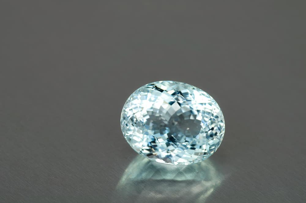 Natural unheated sky blue big topaz oval faceted gemstone. Clean, transparent, huge, sparkling treasure. Gray backgroung. Many facets, cut in Thailand. Original from Brazil.