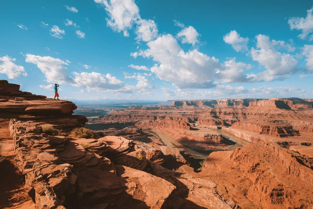 Hiker on a cliff in Dead Horse Point State Park, Utah, USA A young male hiker is standing on the edge of a cliff enjoying a dramatic overlook of the famous Colorado River and beautiful Canyonlands National Park in scenic Dead Horse Point State Park, Utah, USA (A young male hiker is standing on the edge of a c